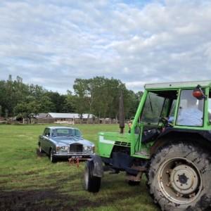 Rolls Royce wordt door een tractor uit de modder gehaald