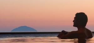 Zwoele zonsondergang in Schotland met toekijkende man