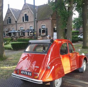 Rode Citroën 2CV met op achtergrond restaurant De Vier Seizoenen in Twello